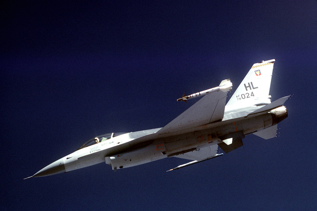 Low angle view of an F-16 Fighting Falcon aircraft armed with an AIM-9 Sidewinder air-to-air (AAM) missile (on the left wing) and an Air Combat Maneuvering Instrumentation pod (A. S. M. I.), (on the right wing) in flight