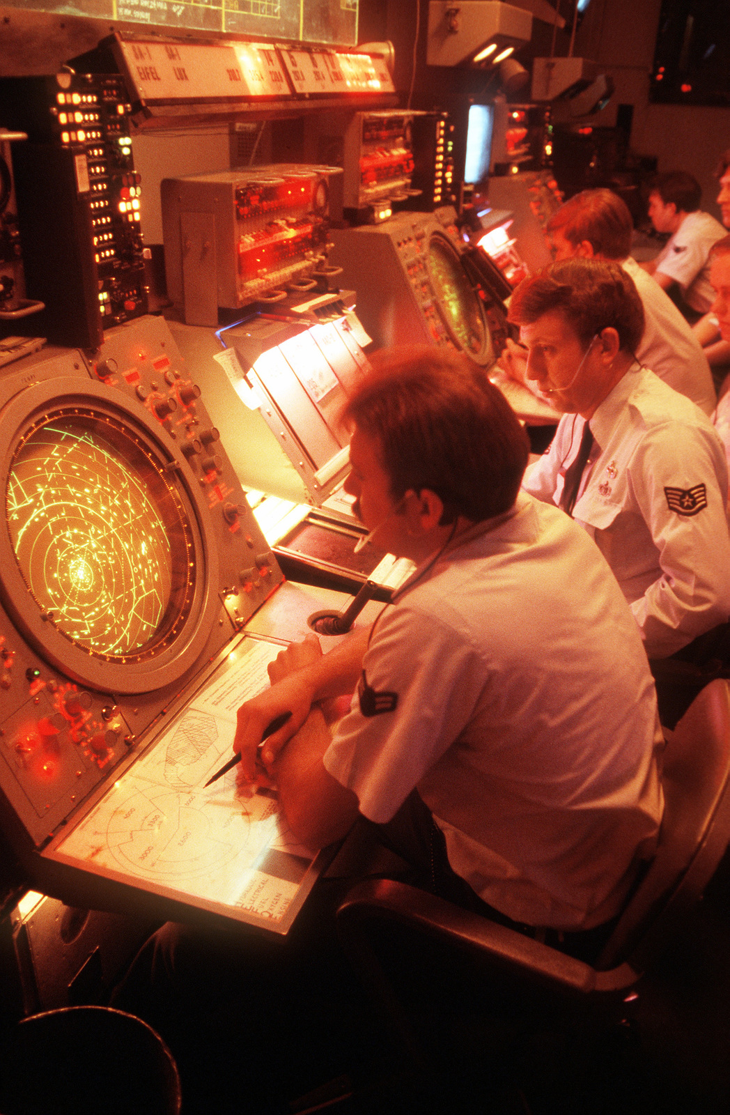 U.S. AIRMAN in the Eifel air traffic control facility, check their radar scopes for air traffic in a 60-mile radius