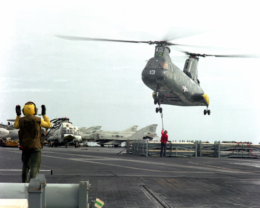 A UH-46 Sea Knight helicopter lowers cargo onto the flight deck of the aircraft carrier USS INDEPENDENCE (CV-62) during vertical replenishment (VERTREP) operations