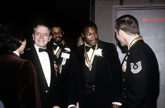 BGEN Cornelius Nugteren, left center, commander, Air Force Air Rescue and Recovery Service, and MSGT Wayne L. Fisk speak with Heavyweight Champion Larry Holmes and his party, prior to the awards ceremony honoring the 10 Outstanding Young Men of the Year. Fisk and Holmes are award recipients