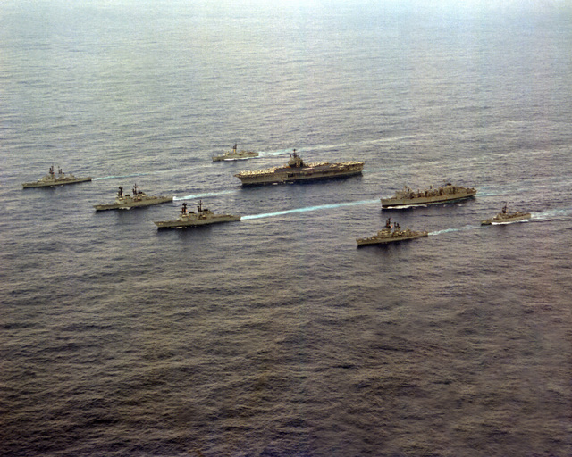 A port bow view of the USS INDEPENDENCE battle group as it heads home from deployment in the Mediterranean Sea. The ships are, clockwise from left, USS FARRAGUT (DDG-37), USS MCCANDLESS (FF-1084), USS INDEPENDENCE (CV-62), USS DETROIT (AOE-4), USS GARCIA (FF-1040), USS MAHAN (DDG-42), USS CARON (DD-970) and USS PETERSON (DD-969)