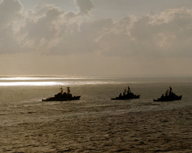 A starboard quarter silhouetted view of five ships in the USS INDEPENDENCE battle group as they head home from deployment in the Mediterranean Sea. The ships are, from left, USS MCCANDLESS (FF-1084), USS PETERSON (DD-969), USS FARRAGUT (DDG-37), USS MAHAN (DDG-42) and USS CARON (DD-970)