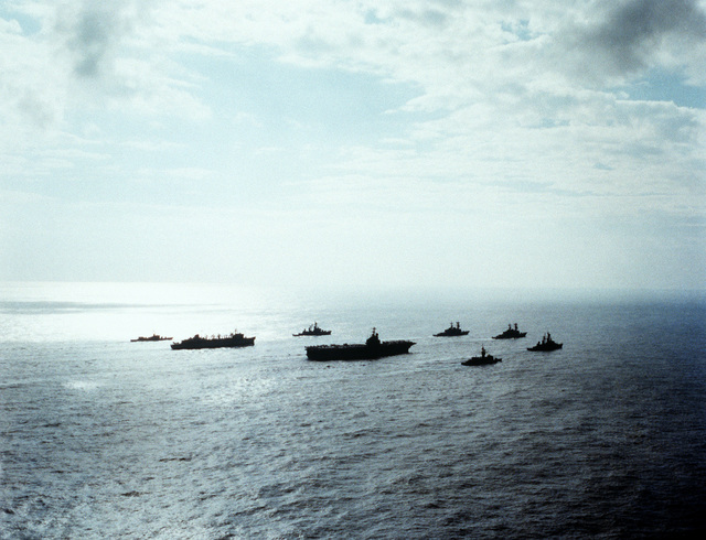 A starboard quarter view of the aircraft carrier USS INDEPENDENCE (CV-62) and its battle group heading home from deployment in the Mediterranean Sea. The ships include, clockwise, from right: the guided missile destroyer USS FARRAGUT (DDG-37), the frigate USS MCCANDLESS (FF-1084), the INDEPENDENCE, the fast combat support ship USS DETROIT (AOE-4), the frigate USS GARCIA (FF-1040), the guided missile destroyer USS MAHAN (DDG-42), the destroyer USS CARON (DD-970) and the destroyer USS PETERSON (DD-969)