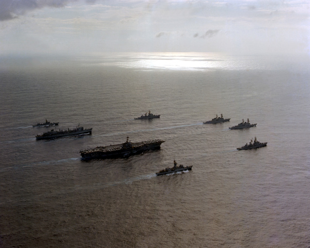 A starboard quarter view of the USS INDEPENDENCE (CV-62) battle group as it heads home from deployment in the Mediterranean Sea. The ships are, clockwise from top, USS MAHAN (DDG-42), USS CARON (DD-970), USS PETERSON (DD-969), USS INDEPENDENCE (CV-62), USS DETROIT (AOE-4) and USS GARCIA (FF-1040)