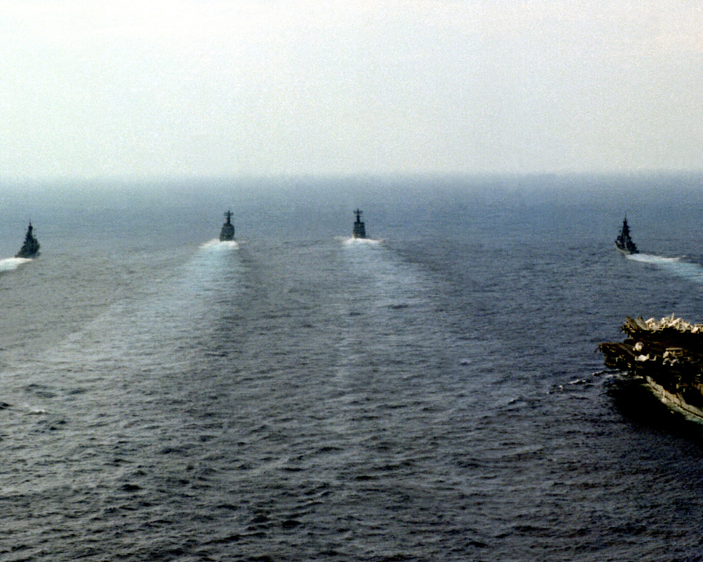 A stern view of the aircraft carrier USS INDEPENDENCE (CV-62), right, and the fast combat support ship USS DETROIT (AOE-4) underway with six escort ships in the lead during the battle group's homeward voyage from deployment in the Mediterranean Sea