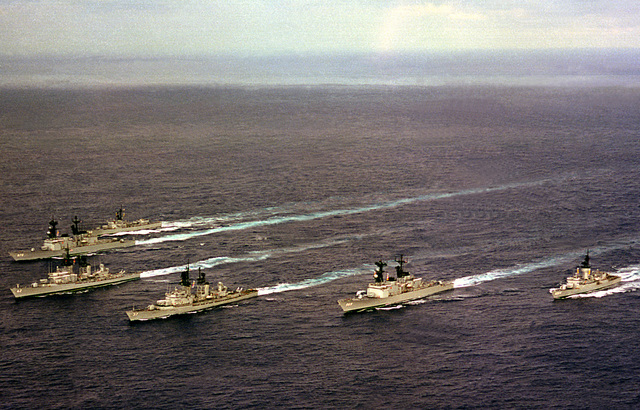 An aerial port bow view of six ships in the USS INDEPENDENCE (CV-62) battle group as they head home from deployment in the Mediterranean Sea. The ships are, clockwise from the right , USS MCCANDLESS (FF-1084), USS PETERSON (DD-969), USS FARRAGUT (DDG-37), USS MAHAN (DDG-42), USS CARON (DD-970) and USS GARCIA (FF-1040)