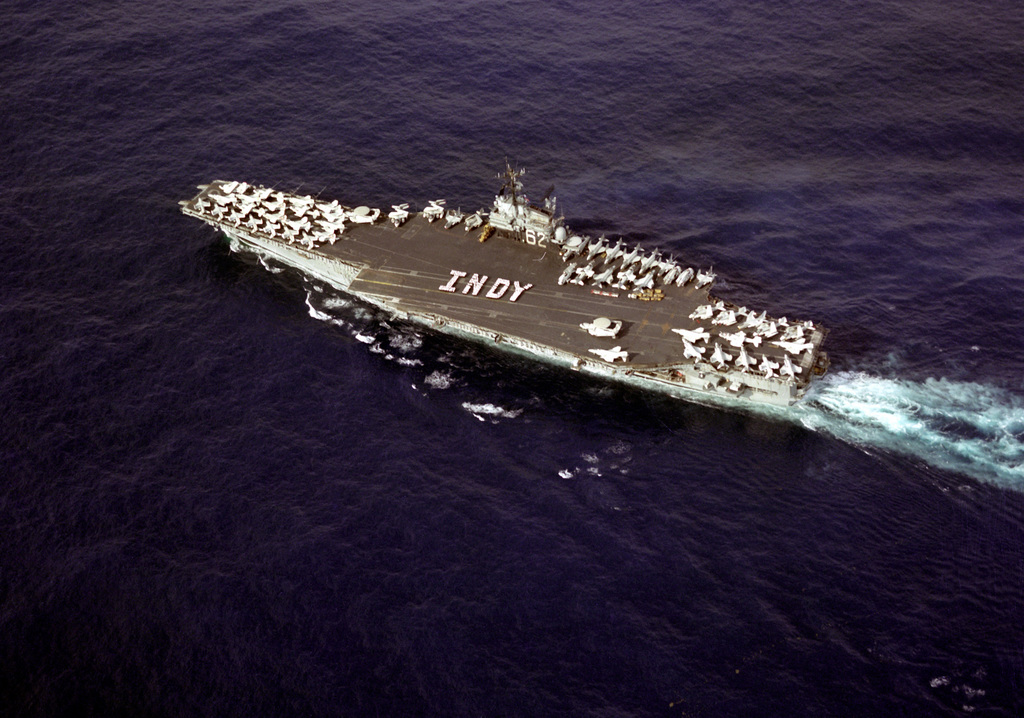 "An overhead view of the aircraft carrier USS INDEPENDENCE (CV-62) underway as crewmen form the word ""Indy"" on the flight deck. The carrier is heading home from deployment in the Mediterranean Sea"