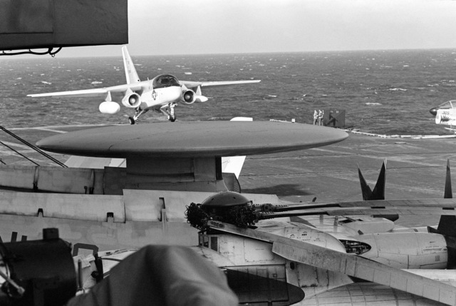 A right front view of an S-3A Viking aircraft as it touches down on the flight deck of the aircraft carrier USS KITTY HAWK (CV 63). Visible in the foreground is the radar dish attached to an E-2C Hawkeye airborne early warning (AEW) aircraft