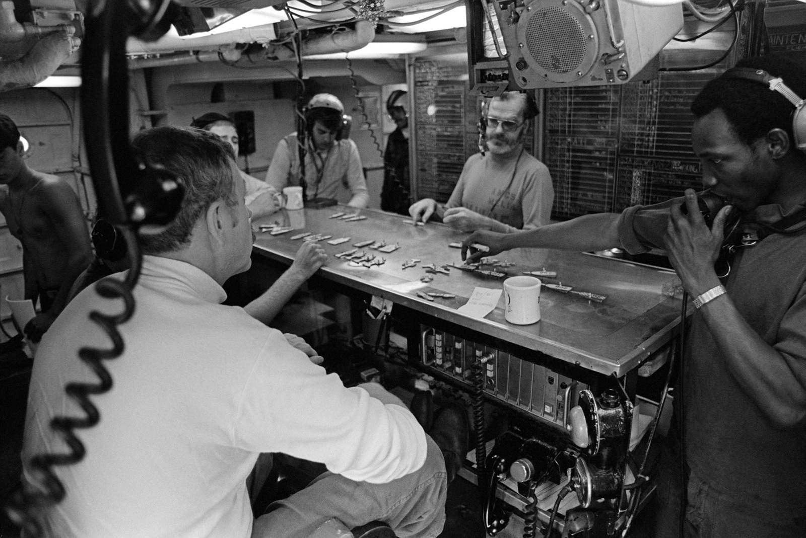 Crewman inside the flight deck control center aboard the aircraft carrier USS KITTY HAWK (CV 63) use a table to simulate the arrangement of aircraft on the carrier's flight deck