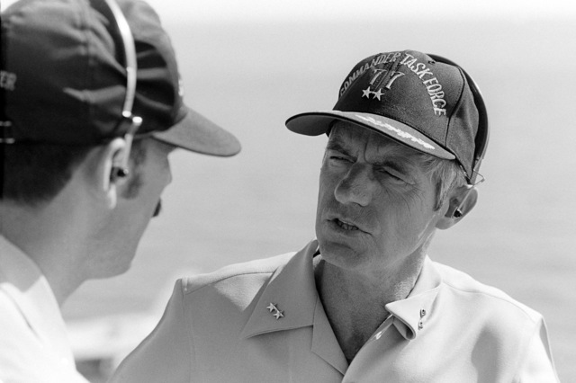 Rear Admiral Robert E. Kirksey, commander, Task Force 77, confers with his aid aboard the aircraft carrier USS KITTY HAWK (CV 63)