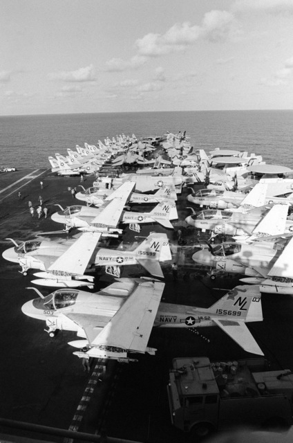 Various aircraft parked in formation aboard the aircraft carrier USS KITTY HAWK (CV 63) include A-6 Intruders, foreground, F-14 Tomcats and A-7 Corsair IIs, background, E-2C Hawkeyes and EA-6B Prowlers, right