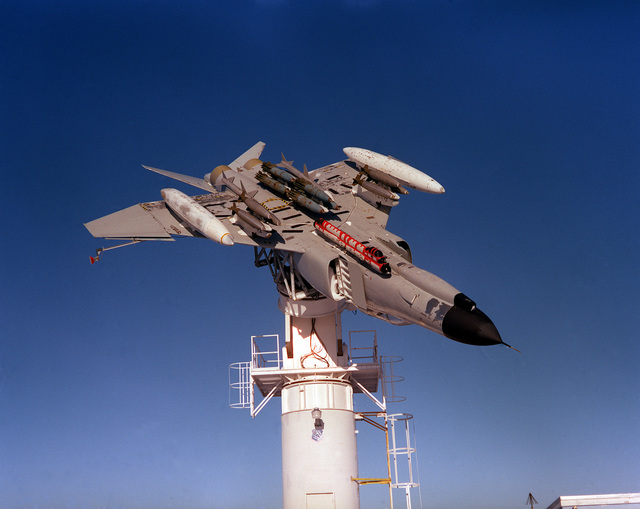 A view of an F-4 Phantom II aircraft mounted upside-down on a test tower at the Rome Air Development Center Antenna Patterns Test Facility at the Newport site. The effectiveness of an AN/ALQ-119 electronic countermeasure pod, attached to the undercarriage of the F-4 is being determined without the aircraft being in flight