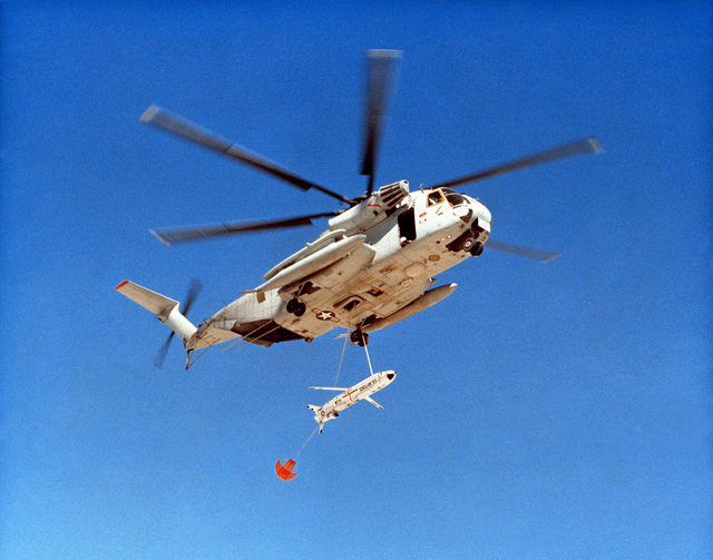 A CH-53C Mid-Air Recovery System (MARS) helicopter recovers and AGM-86B Cruise Missile after termination of test flight. Missile can be examined and possibly used in future tests