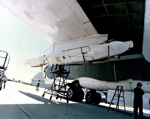 A close-up view of an air-launched cruise missile mounted beneath the wing of a parked B-52 Stratofortress aircraft