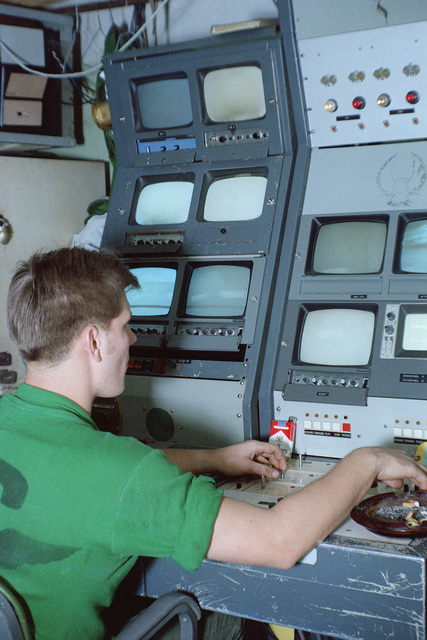 A crewmember mans his plat camera monitoring station on board the aircraft carrier USS CORAL SEA (CV 43)