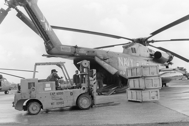 A forklift is used to load cargo aboard an RH-53D Sea Stallion helicopter from Fleet Logistics Support Support Squadron 24 (VR-24)