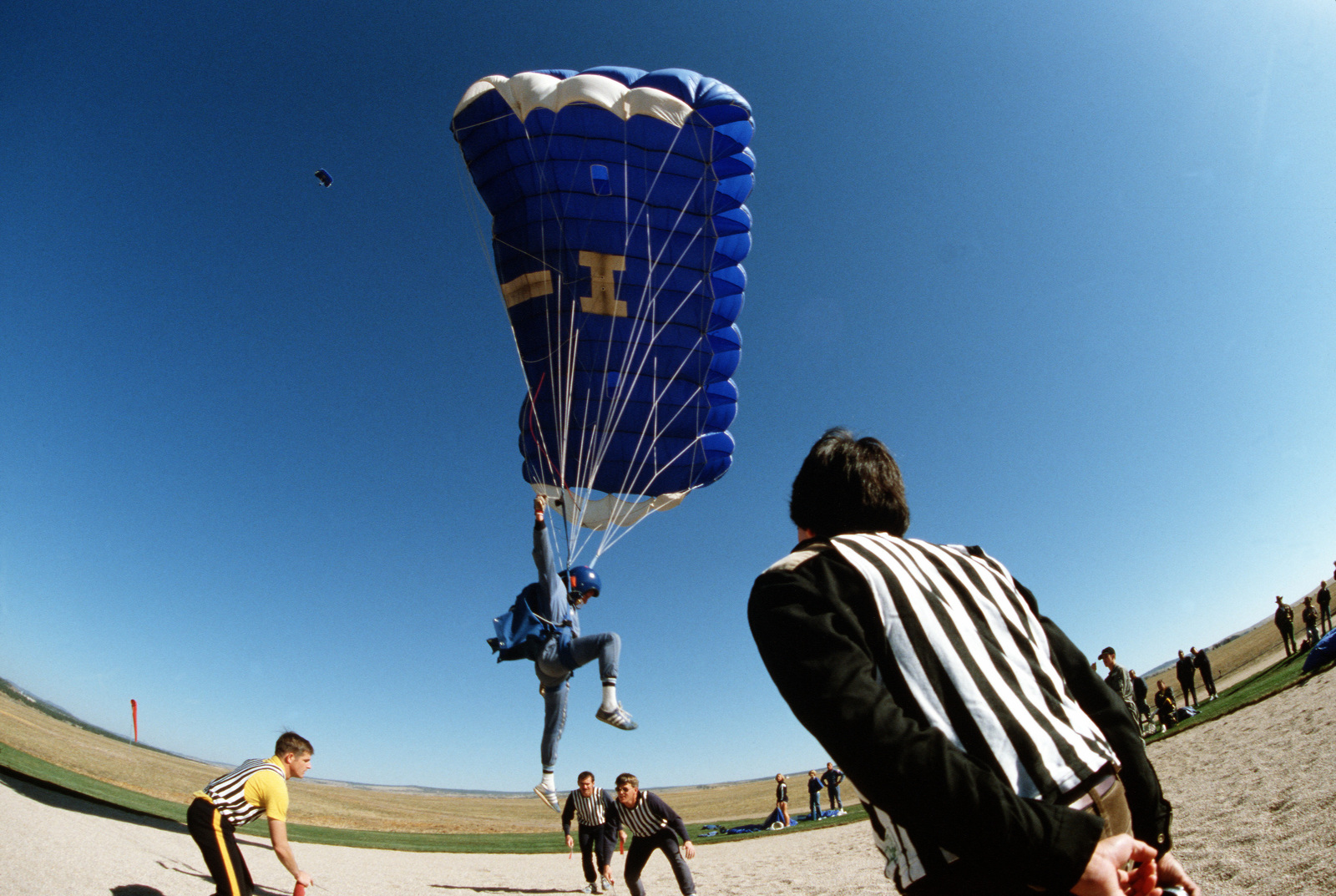 A service school parachute team member maneuvers to hit a metal disc in the target circle during the 1980 Tri-Service Parachute Tournament