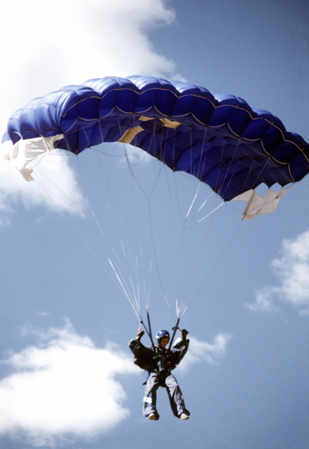 A service school parachute team member nears the ground during the 1980 Tri-Service Parachute Tournament