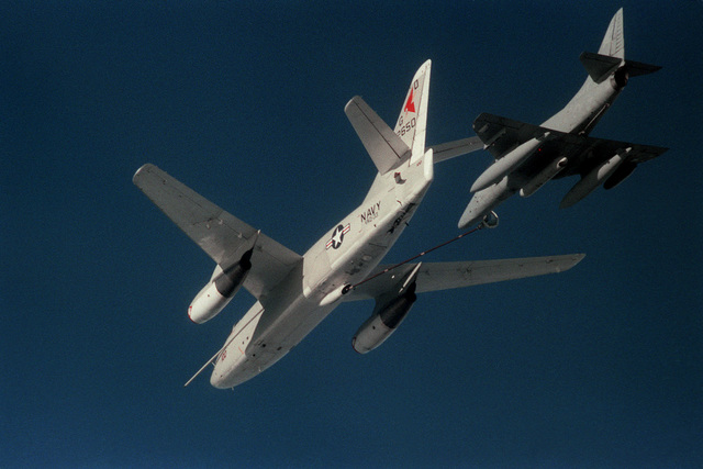 Aerial underside view of an EA-3B Skywarrior aircraft of Tactical Electronic Warfare Squadron Thirty Three (VAQ-33) refueling a TA-4J Skyhawk aircraft of Composite Squadron Twelve (VC-12). Exact Date Shot Unknown