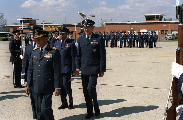 Air Marshall Panieng Karntarat of Thailand is escorted from his plane by GEN Lew Allen, center, U.S. Air Force chief of staff, after his arrival in the United States for a visit