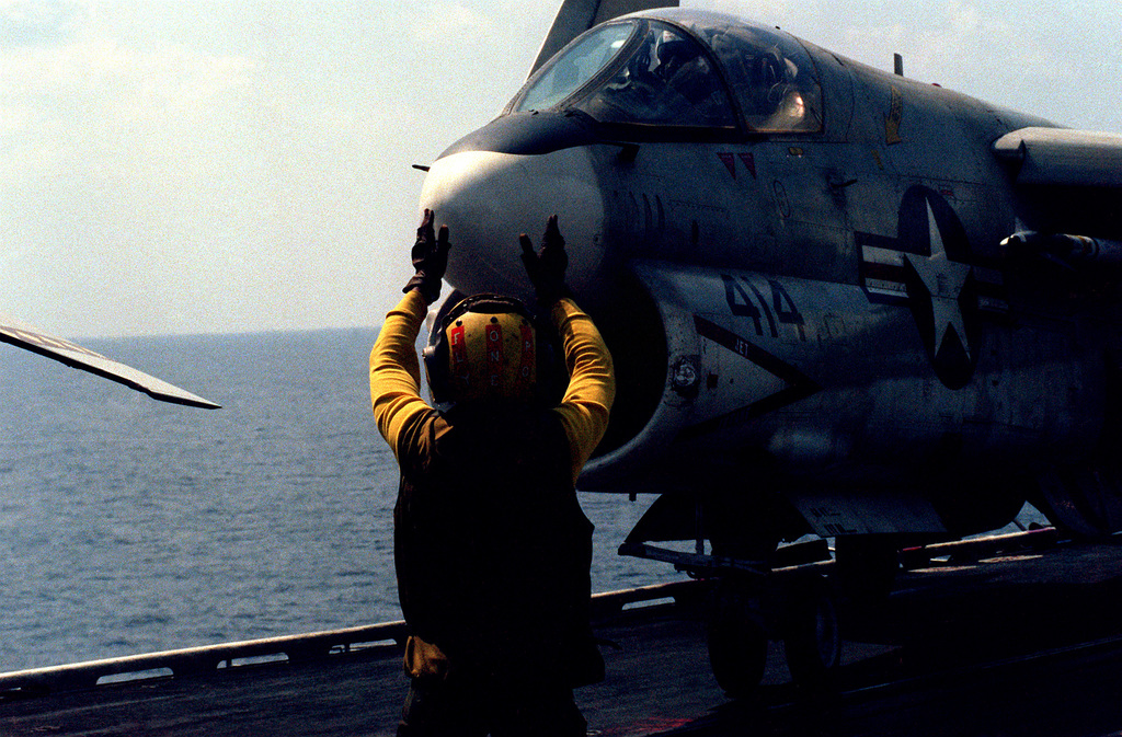 An A-7 Corsair II attack aircraft from Light Attack Squadron 27 (VA-27) is directed by a flight deck crewman aboard the aircraft carrier USS CORAL SEA (CV-43)