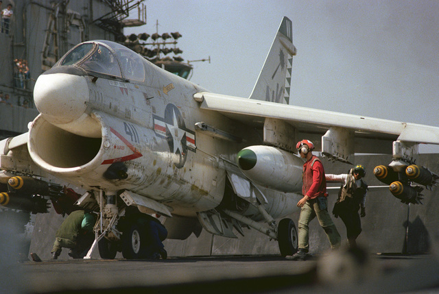An A-7 Corsair II attack aircraft is prepared for launch aboard the aircraft carrier USS CORAL SEA (CV 43). The aircraft is armed with Mk-82 high drag bombs