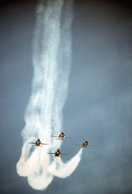 An air-to-air front view of four Thunderbirds T-38 Talon aircraft maneuvering in a circle during a demonstration