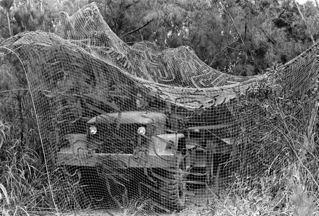 An M-48 tractor attached to a flatbed trailer is covered with a large camouflage net during Marine training at the Central Training Area. The Marines are a part of the 3rd Marine Division