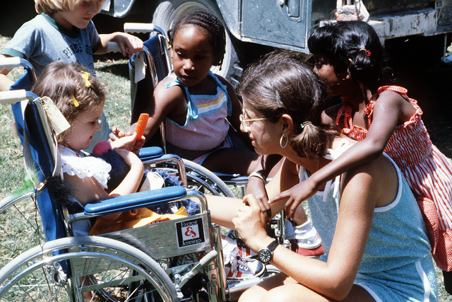 An officer in the Air Force shares her off-duty time with young campers. Children's Association for Maximum Potential (CAMP) developed a camp program for handicapped youngsters
