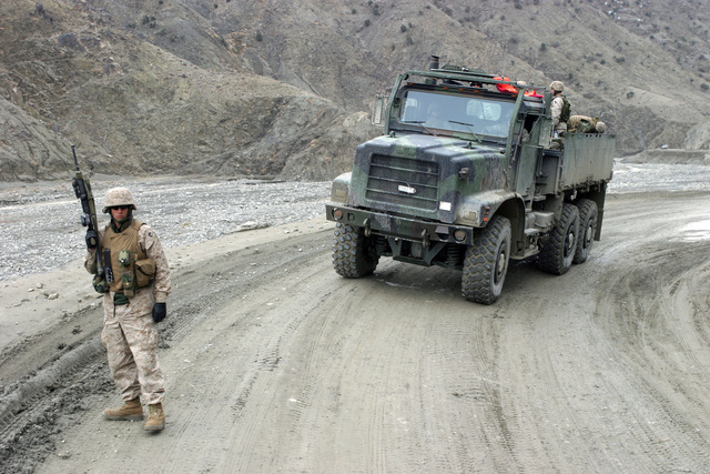 Armed with a Colt 5.56mm M16A2 Assault Rifle, a U.S. Marine Corps troop with Weapons Company, 3rd Battalion, 3rd Marine Regiment, provides security for a Medium Tactical Vehicle Replacement 7-ton truck in the Khowst-Gardez Pass, Afghanistan, on Dec. 30, 2004.  These Marines are conducting security and stabilization operations in support of Operation Enduring Freedom.  (U.S. Marine Corps PHOTO by CPL James L. Yarboro) (Released)