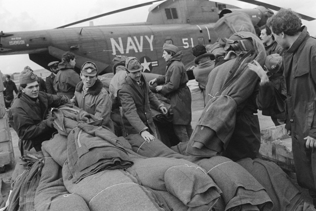 Blankets and other supplies are unloaded from an RH-53D Sea Stallion helicopter assigned to Fleet Logistics Support Squadron 24 (VR-24)