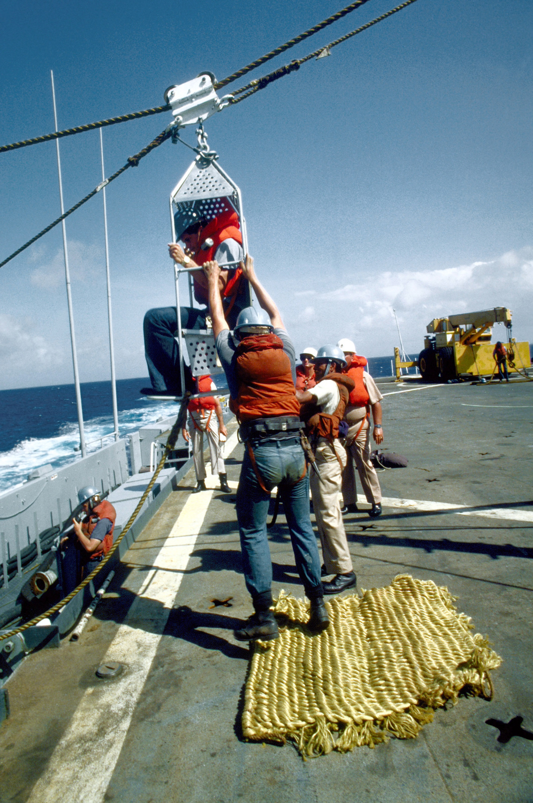 Crewmen aboard the destroyer USS ARTHUR W. RADFORD (DD-968) pull a boatswain's chair to the deck during a personnel transfer by highline from the guided missile destroyer USS KING (DDG-41). The ships are taking part in exercise Unitas XXI