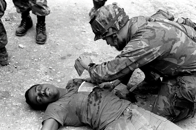 "During 3rd Combat Engineer Battalion's mass casualty field training at the Central Training Area, LCPL Pete Goodson is one of the ""casualties"" with a chest wound. He is attended to by Hospitalman Ray Werts of Charlie Company"