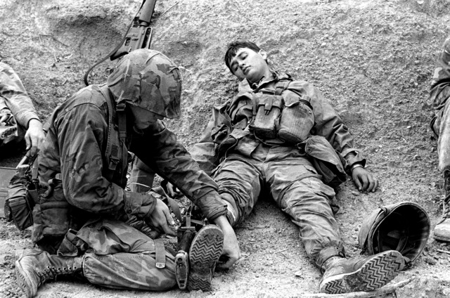 During 3rd Combat Engineer Battalion's mass casualty field training at the Central Training Area, LCPL Pete Leyva is one of the make believe casualties with a fractured leg. PFC Russell Boyes tends to Leyva's leg by using his rifle as a splint