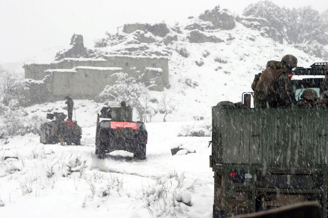 During a snow storm, U.S. Marines Corps personnel mounted on High-Mobility Multipurpose Wheeled Vehicles (HMMWV) from a Weapons Company with the 3rd Battalion, 3rd Marine Regiment, head down a narrow stretch of road while in route to the Khowst-Gardez Pass in Afghanistan, on Dec. 28, 2004.  These Marines are conducting security and stabilization operations in support of Operation Enduring Freedom. (U.S. Marine Corps PHOTO by CPL James L. Yarboro) (Released)