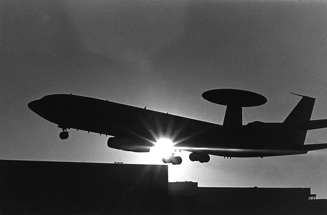 Left side view of an E-3A Airborne warning and control system aircraft, silhouetted against the sunset, taking off on a mission to Ramstein Air Base, West Germany. The aircraft will participate in a joint training exercise with elements of the NATO air-defense system in central Europe