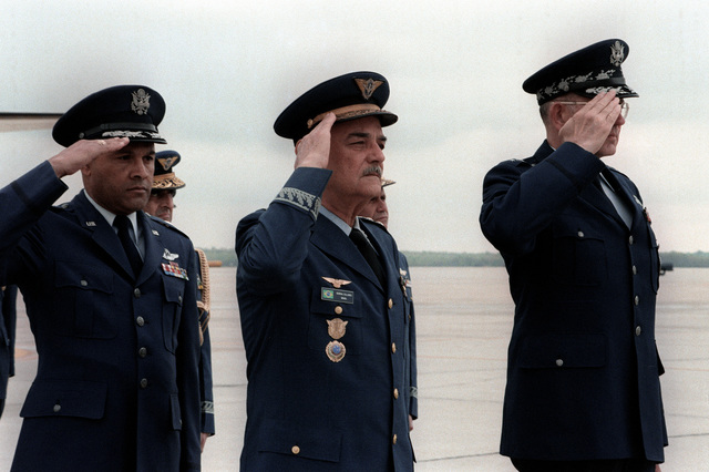 LGEN Leonardo T. Collaces, Brazil air force chief of staff, center, standing by GEN Lew Allen, U.S. Air Force chief of staff, salutes a U.S. flag upon his arrival to the United States for a visit