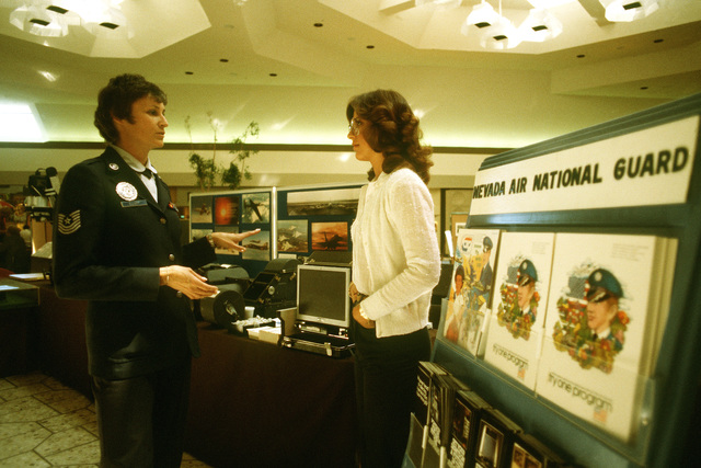MSGT Marcia M. Elliott describes a reconnaissance mission to a tourist at a display in a shopping mall. Elliott is a recruiter from the 152nd Tactical Reconnaissance Group, Nevada Air National Guard