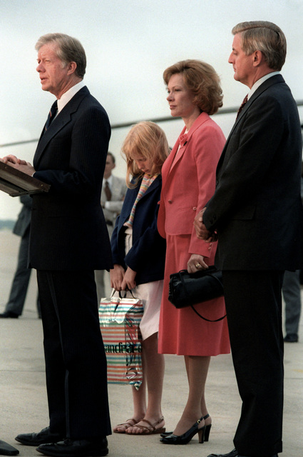 Rosalyn Carter, daughter Amy Carter and Vice President Walter Mondale listen as President Jimmy Carter speaks to a crowd upon his return from a European visit