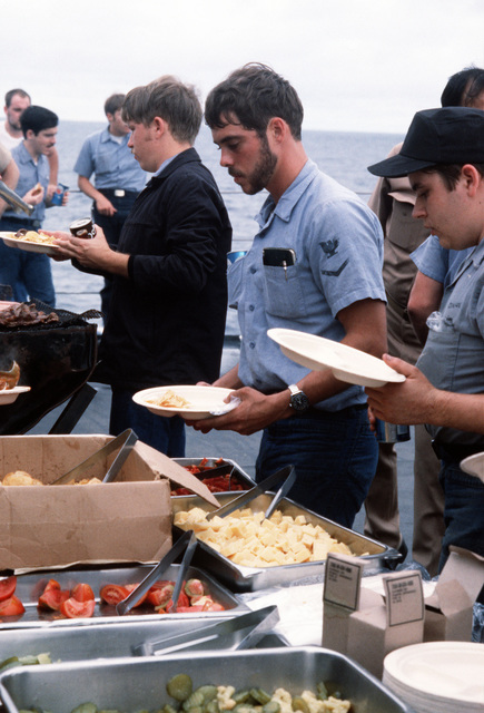 Sailors aboard the destroyer USS RADFORD (DD 968) line up to fill their plates at a picnic lunch fixed for them during exercise Unitas XXI
