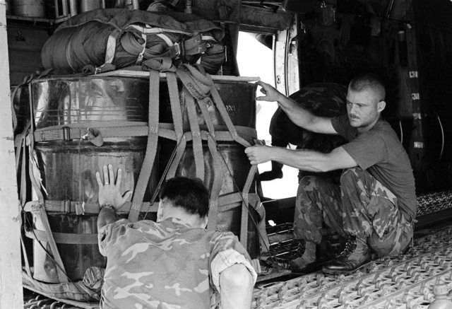 SGT Aguus R. Keydeniers gives SGT Robert C. Bunce a helping hand at loading a pallet of 50-gallon drums onto a C-130 Hercules aircraft