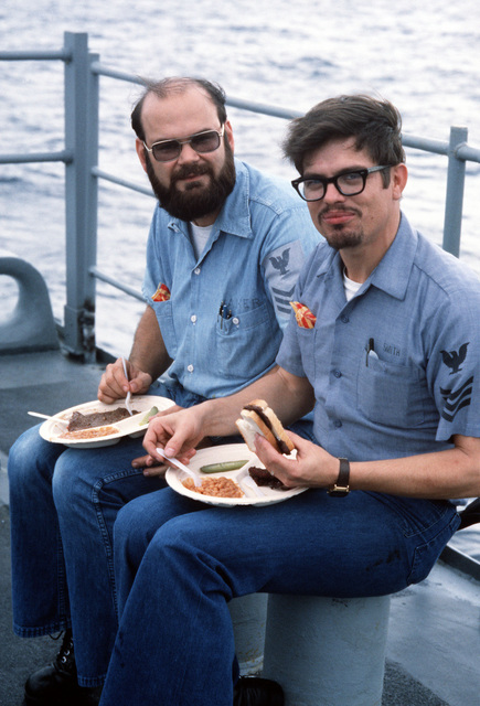 Two crewmen eat a picnic lunch fixed for the men aboard the destroyer USS RADFORD (DD 968) during exercise Unitas XXI