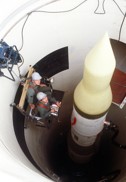 Two missile maintenance crewmen perform an electrical check on an LGM-30F Minuteman III intercontinental ballistic missile (ICBM) in its silo
