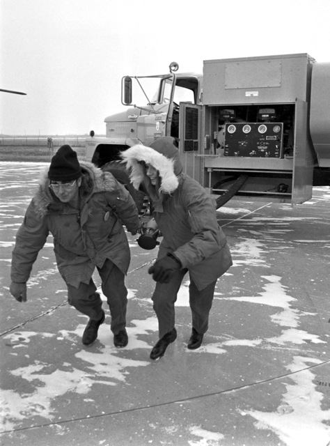 """U.S. Air Force Fuel Specialists Merrill R. Knodle, (left) and Barbara Wiedmeier, assigned to the 119th Fighter Wing""""Happy Hooligans"""", North Dakota Air National Guard, pull a fuel hose at Hector International Field, North Dakota. (A3604) (U.S. Air Force PHOTO) (Released)"""