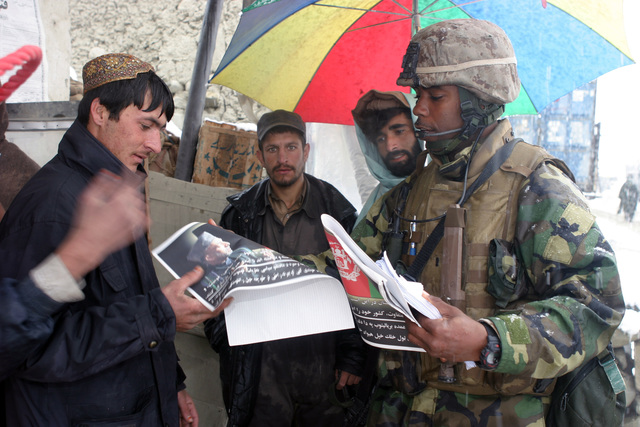 U.S. Marine Corps 1ST LT. Nick Ramseur, a platoon commander with Weapons Company, 3rd Battalion, 3rd Marine Regiment, hands out posters and flyers to the local people in a mountain village at the Khowst-Gardez Pass, Afghanistan, on Dec. 31, 2004.  These Marines are conducting security and stabilization operations in support of Operation Enduring Freedom.  (U.S. Marine Corps PHOTO by CPL James L. Yarboro) (Released)