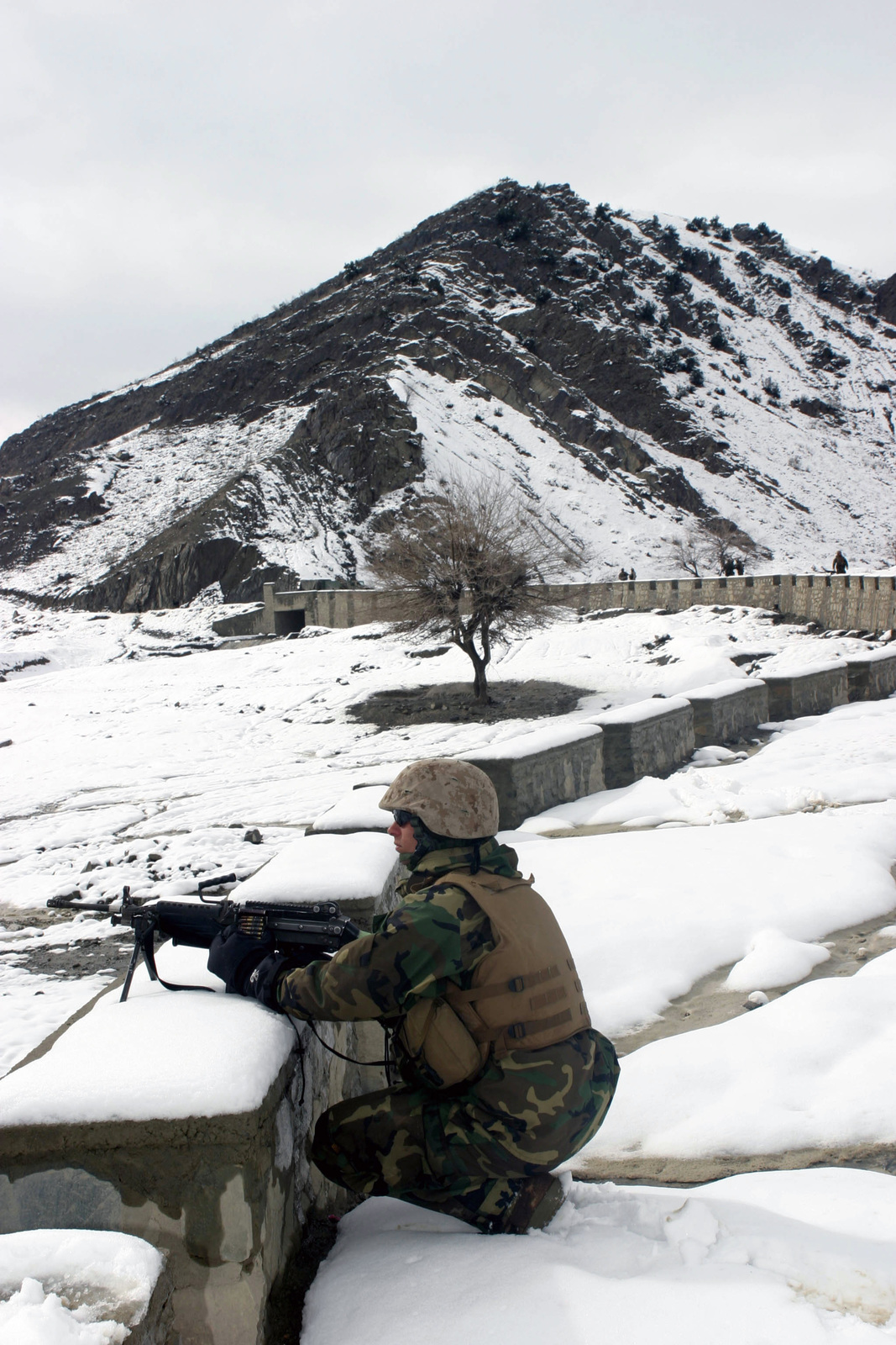 U.S. Marine Corps PFC. Adam Brantley, a rifleman with Weapons Company, 3rd Battalion, 3rd Marine Regiment, provides security behind his FNMI 5.56mm M249 Squad Automatic Weapon (SAW) during on a long security halt in the Khowst-Gardez Pass, Afghanistan, on Dec. 29, 2004.  These Marines are conducting security and stabilization operations in support of Operation Enduring Freedom.  (U.S. Marine Corps PHOTO by CPL James L. Yarboro) (Released)