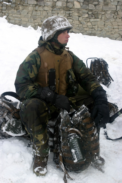 U.S. Marine Corps PFC. Adam Brantley, a rifleman with Weapons Company, 3rd Battalion, 3rd Marine Regiment, sits on his pack and on deep snow while waiting for the plan of the day in the Khowst-Gardez Pass, Afghanistan, on Dec. 29, 2004.  These Marines are conducting security and stabilization operations in support of Operation Enduring Freedom.  (U.S. Marine Corps PHOTO by CPL James L. Yarboro) (Released)