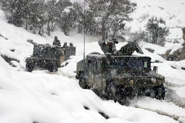 U.S. Marine Corps troops in High-Mobility Multipurpose Wheeled Vehicles (HMMWV) of Weapons Company, 3rd Battalion, 3rd Marine Regiment, conduct a mounted patrol in the cold and snowy weather of the Khowst-Gardez Pass, Afghanistan, in order to disrupt any enemy activity on Dec. 30, 2004. These Marines are conducting security and stabilization operations in support of Operation Enduring Freedom.  (U.S. Marine Corps PHOTO by CPL James L. Yarboro) (Released)