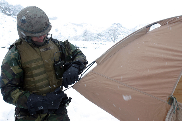 U.S. Navy PETTY Officer 3rd Class Will Hurley, a Hospital Corpsman with Weapons Company, 3rd Battalion, 3rd Marine Regiment, sets up a tent for protection from the cold weather in the Khowst-Gardez Pass, Afghanistan, on Dec. 29, 2004.  These Marines are conducting security and stabilization operations in support of Operation Enduring Freedom.  (U.S. Marine Corps PHOTO by CPL James L. Yarboro) (Released)