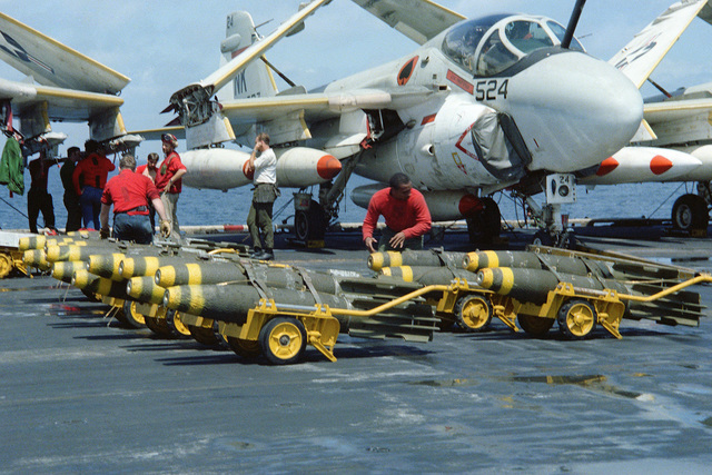 Weapons department personnel move Mk 82 500 pound general purpose 500 pound bombs aboard the aircraft carrier USS CORAL SEA (CV 43) during her 1979-1980 deployment. An A-6 Intruder attack aircraft is parked in the background